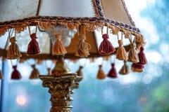 棕色缨子特写镜头在古色古香的灯罩的有华丽古铜色脚灯元素和模糊的背景的 葡萄酒灯细节 库存图片