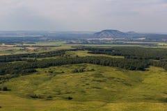 森林、领域和两唯一山风景  免版税库存图片