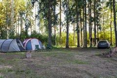森林两帐篷和汽车的停放的游人 免版税库存图片