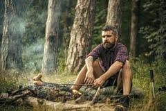 森林别动队员 行家远足者在棍子的烘烤香肠在火在森林里 库存照片