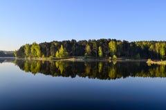 森林和天空在森林湖的镇静大海被反射 在美丽的鸟云彩之上颜色及早飞行金子早晨本质宜人的平静的反映上升海运一些星期日 免版税库存图片