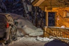 森林村庄和一辆汽车在一个冬天晚上 库存照片