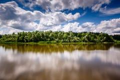 森林条纹在多云天空和河之间的在莫斯科附近 库存照片