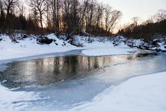 森林流雪河岸在冬天 免版税图库摄影