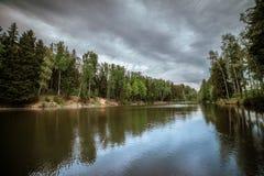 森林湖的美好的风景 与银色纹理云彩的多云天气 惊人风景 树被反射 库存图片