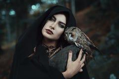 森林的黑暗的巫婆有她的猫头鹰的 免版税图库摄影