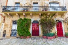 森格莱阿,马耳他-传统红色门和房子在森格莱阿街道上  图库摄影