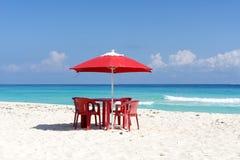 椅子、桌和伞在一个热带海滩 库存图片