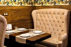 椅子和沙发在一个咖啡馆在玻璃桌上  免版税库存图片