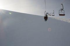 椅子在日落的滑雪电缆车 免版税图库摄影