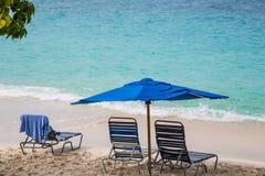 椅子在海滩的蓝色伞下 免版税库存照片