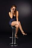 椅子性感的坐的太阳镜妇女 免版税库存图片