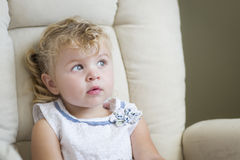 椅子的传神白肤金发的头发和蓝眼睛的小女孩 免版税库存图片