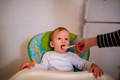 椅子的哺养的饥饿的小孩子 免版税库存图片