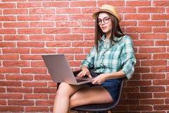 椅子的妇女在便衣使用一台膝上型计算机 图库摄影
