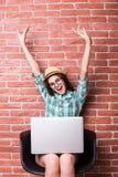 椅子的妇女在便衣使用一台膝上型计算机 免版税库存图片