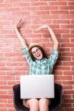 椅子的妇女在便衣使用一膝上型计算机和微笑疲乏的工作 库存照片