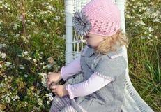 椅子的小白种人女孩在野花 免版税库存图片