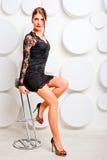 椅子的迷人的女孩在鞋带礼服 免版税图库摄影