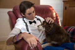 椅子的青少年的男孩与在他的膝部的狗 库存图片