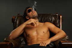 椅子的年轻人抽烟 库存图片