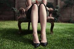 椅子老坐的妇女庭院 库存图片