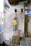 椅子街道艺术壁画的男孩在乔治城,槟榔岛,马来西亚 免版税库存照片