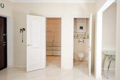 椅子门入口房子内部现代红色 入有白色门的走廊对可容人走进去的大壁橱和洗手间 库存照片