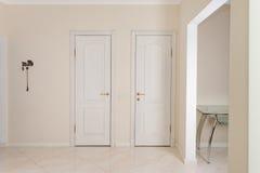 椅子门入口房子内部现代红色 入有白色门的走廊对可容人走进去的大壁橱和洗手间 库存图片