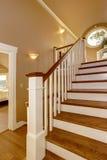 椅子门入口房子内部现代红色 有木楼梯和白色栏杆的走廊 免版税库存照片