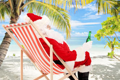 椅子饮用的啤酒的圣诞老人和享用在海滩 免版税图库摄影