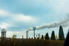 植物管子的一个大计划,在环境里生产有害的烟以天空为背景 图库摄影
