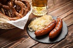 椒盐脆饼、多味腊肠和德国泡菜在木桌上 免版税库存图片