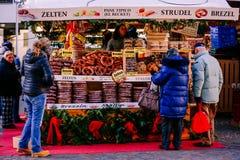 椒盐脆饼,果馅奶酪卷和其他典型的产品在传统圣诞节市场上 女低音阿迪杰,意大利 库存图片