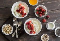 椰奶甜米粥用在木背景,顶视图的莓果 健康面筋免费素食早餐 免版税库存图片