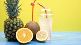 椰子、切的桔子和柠檬和一个菠萝在塑料杯子旁边用新鲜的汁液 影视素材