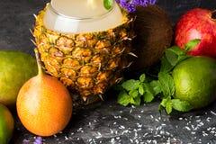 椰子、菠萝、柑橘、石榴石和装饰花在黑背景 不同的异乎寻常的果子的构成 免版税库存图片