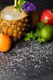 椰子、菠萝、柑橘、石榴石和装饰花在黑背景 不同的异乎寻常的果子的构成 库存照片