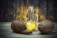 椰子和一个瓶在木桌上的椰子油 免版税库存图片