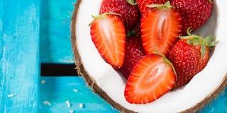 椰子和草莓在明亮的蓝色 免版税库存图片