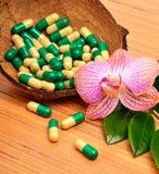 椰子壳,胶囊,片剂,兰花花 免版税库存照片