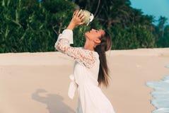 椰子水流量特写镜头在一个年轻欧洲女孩的面孔和脖子的有黑发的 在海滩的一个模型 库存图片