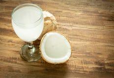 椰子汁和椰子在木背景 免版税库存照片