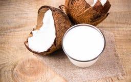 椰子用在木背景的椰奶 免版税库存图片