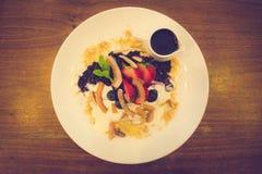 椰子面粉薄煎饼蓝莓蜜饯,新鲜的香蕉鞭打了希腊酸奶 免版税库存图片