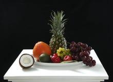 从椰子,菠萝,成熟的各种各样的新鲜水果,苹果和葡萄在白色桌上在黑背景中健康的 库存照片