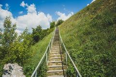 楼上人造楼梯对与绿草、旅行和旅游业概念的小山 免版税库存照片