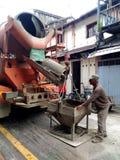楼房建筑工作者倾吐的水泥或混凝土与泵浦管 免版税库存图片