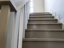 楼梯在现代新房里 现代两口气楼梯在房子,木楼梯灰色步里 图库摄影