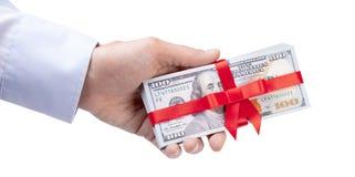 概念、金钱作为礼物,胜利或者奖金 人在衬衣的` s手采取或给堆100美金栓与与弓的红色丝带 免版税图库摄影
